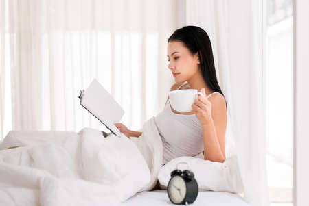 Happy beautiful asian woman drinking coffee and reading book on bed,Happy and smiling,Positive thinking,Relax time