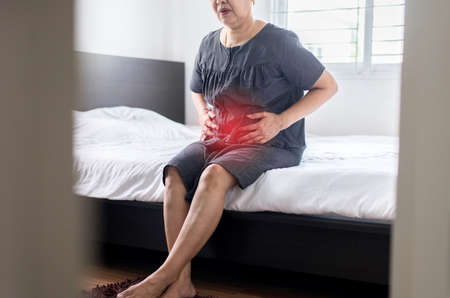 Elderly asian woman having painful  at home,Senior female suffering from abdominal pain Stok Fotoğraf