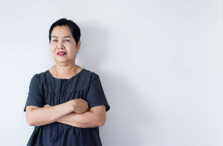Portrait of beautiful elderly asian woman standing cross arms and looking camera indoor,Happy and smile face,Copy space for text on white background