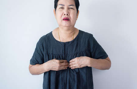 Senior asian woman having or symptomatic reflux acids,Gastroesophageal reflux disease,Copy space on white background