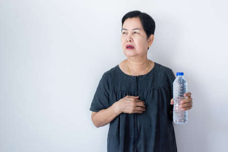 Senior asian woman having or symptomatic reflux acids,Gastroesophageal reflux disease,Drinking water