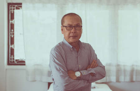 Portrait of senior asian man standing cross arms and looking camera indoor