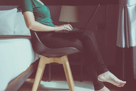 Woman working on laptop while sitting on chair at home,Happy and smiling,Enjoying time,Close up