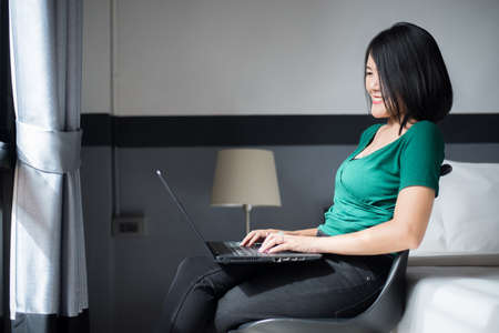Beautiful young asian woman working on laptop while sitting on chair at home with flare light,Happy and smiling,Enjoying time