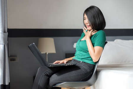 Close up of woman working on laptop while sitting on chair in bedroom with flare light,Happy and enjoying time,Positive thinking