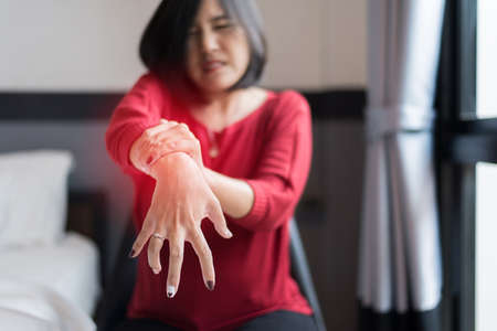 Woman suffering with parkinson's disease symptoms,Selective focus hands