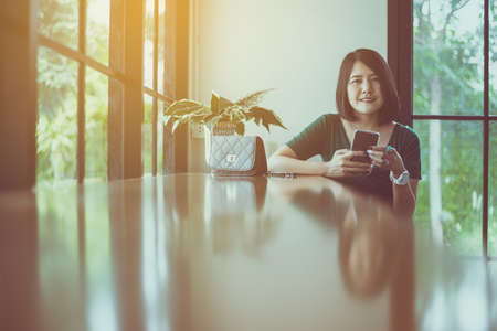 Beautiful asian woman using cell phone at cafe in the morning, Happy and smiling, Positive thinking