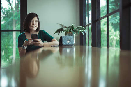Beautiful asian woman using cell phone in coworking spaces, Happy and smiling, Positive thinking,Good health