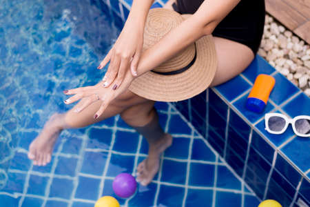 Woman hands applying sunscreen cream,Female using sunblock at swimming pool,Summer travel concept