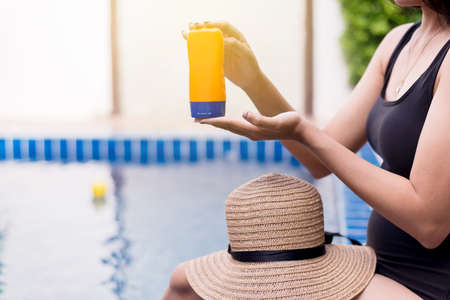 Woman hands holding sunscreen cream,Female using sunblock at swimming pool,Summer travel concept