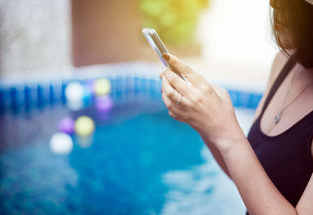 Beautiful asian woman using mobile phone at swimming pool,Happy and smiling,Relax time,Summer travel concept Stock Photo - 129877303