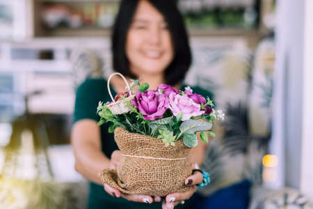 Woman hand holding beautiful flower in sack bag,Happy and smiling,Selective focus,Close up Stock Photo - 129877307