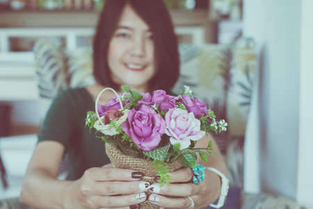 Woman hand holding beautiful flower in pot,Happy and smiling,Selective focus,Close up Stock Photo - 129877308