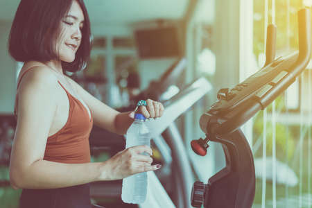 Attractive woman sitting and drinking water in gym,Asian female break and relax after workout Stock Photo - 129877311