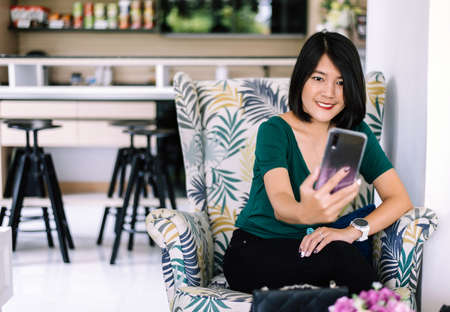 Portrait of beautiful asian woman short hair selfie mobile while sitting on sofa in the restaurant,Happy and smiling,Positive thinking Stock Photo - 129877315
