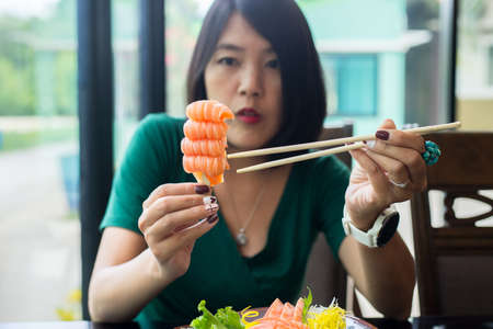 Hands woman using chopsticks with fresh salmon sashimi in restaurant