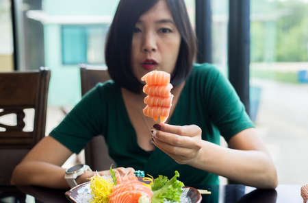 Hands woman holding fresh salmon sashimi in restaurant
