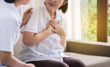 Ältere asiatische Frau mit Brustschmerzen, die an Herzinfarkt leidet, Krankenschwester kümmert sich um und unterstützt Standard-Bild
