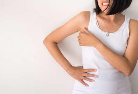 Asiatische Frau mit Geruchsschwitzen,Weibchen, die an ihrer Achsel riechen oder schnüffeln,schlechter Geruch,Nahaufnahme