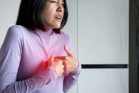Asian woman having or symptomatic reflux acids,Gastroesophageal reflux disease,Because the esophageal sphincter that separates the esophagus and stomach dysfunction Stock Photo - 129881999