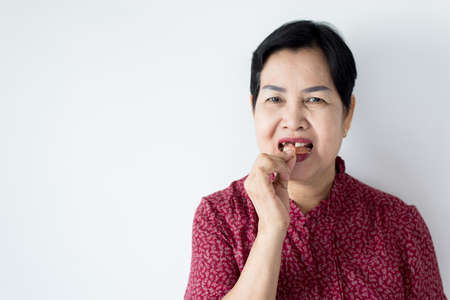 Senior asian woman is holding dentures in hands,Dental prosthesis,False teeth Stock Photo - 129882010