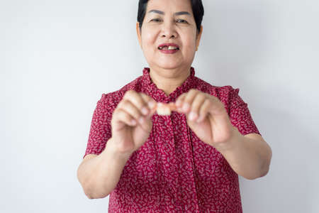 Blured of senior asian woman is holding dentures in hands,Dental prosthesis,False teeth,Selective focus
