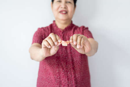 Senior asian woman is holding dentures in hands. Dental prosthesis,False teeth,Close up