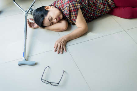 Senior asian woman suffering with faint lying on floor after falling down at home Stock Photo