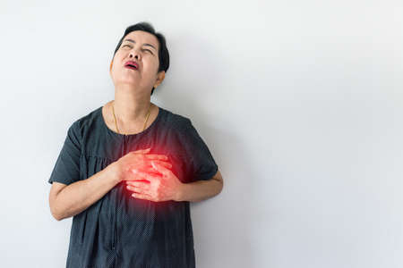 Elderly asian woman having chest pain suffering from heart attack on white background,Copy space for text