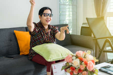 Happy elderly asian woman watching television on the couch in the living room at home Stock Photo