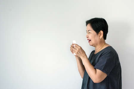 Flu senior asian woman and using tissue paper,Elderly female sneezing,Copy space for text on white background Stock Photo - 129884638