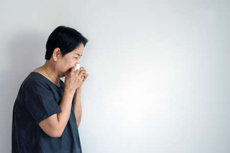 Flu senior asian woman and using tissue paper,Elderly female sneezing,Copy space for text on white background