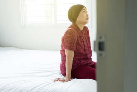 Senior asian woman with disease cancer sitting in her bedroom,Elderly female feeling depressed and upset,Chemotherapy concept 스톡 콘텐츠