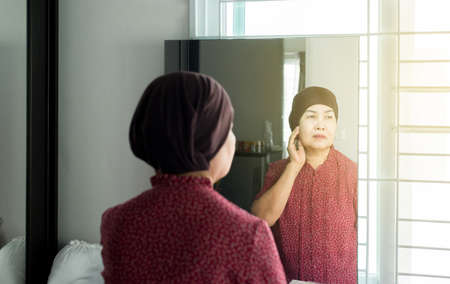 Chemotherapy concept,Senior asian woman with disease cancer standing and looking something in her bedroom,Elderly female feeling depressed and upset