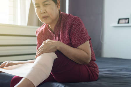 Senior asian woman using elastic bandage with leg,Female putting bandage on her injured knee