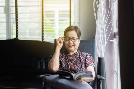 Mature asian woman wearing glasses and reading a book at home,Relax time,Senior lifestyle concept