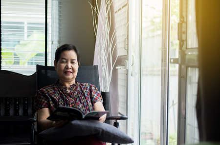 Mature asian woman reading a book at home,Relax time,Senior lifestyle concept Stock Photo