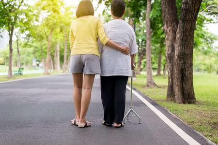 Ältere asiatische Frauen, die mit dem Stock im Park physisch gehen, Tochter kümmern und unterstützen