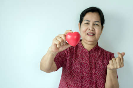 Senior asian woman hands holding red heart model,Health Care and cardiology concept,Copy space for text on white background