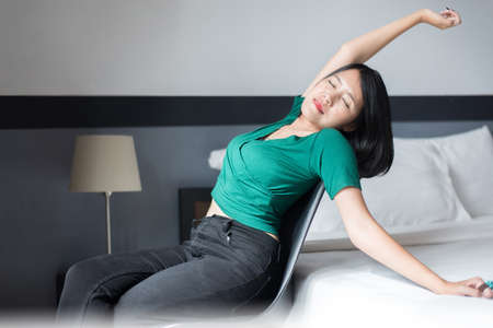 Happy asian woman relaxing and stretch lazily in bedroom at home