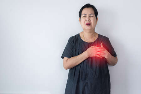 Elderly Asian woman having chest pain suffering from heart attack on white background, Copy space for text Stock Photo