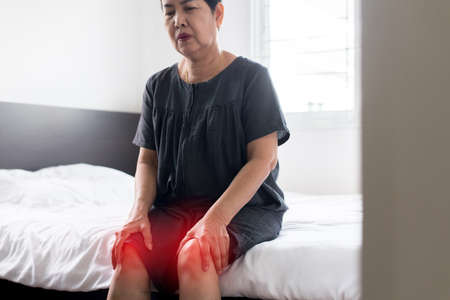 Senior asian woman suffering on legs pain, Female touching her injured knee