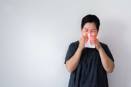Flu senior Asian woman and using tissue paper, Elderly female sneezing, Copy space for text on white background