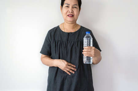 Senior Asian woman having or symptomatic Reflux acids, Gastroesophageal Reflux disease, Drinking water, Copy space on white background 版權商用圖片