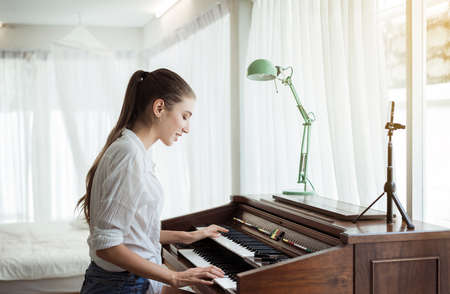Beautiful Caucasian young woman playing electric piano, Happy and smiling, Relaxing time