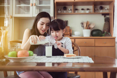 Asian single mother helping little daughter putting milk to glass with breakfast together at home kitchen in the morning