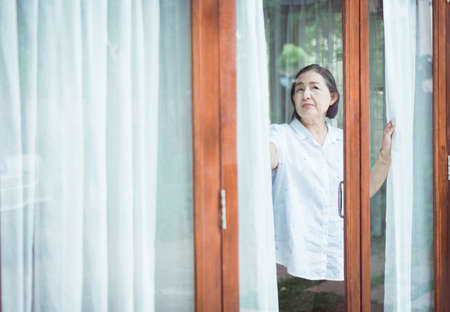Senior healthy concept, Mature Asian elderly woman having migraine and looking something near window at home