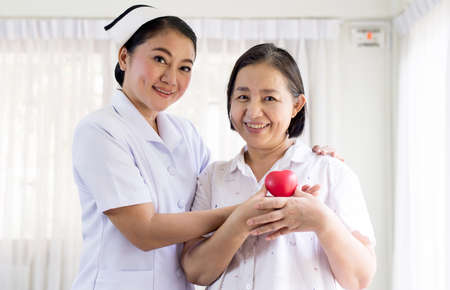 Nurse and Asian elderly woman holding heart red model on hands together, Senior healthy and taking care concept Stock Photo