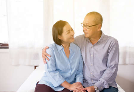 Happy Asian senior couple encourage and  hands holding on bed together, Happy and smiling,Positive thinking Stock Photo