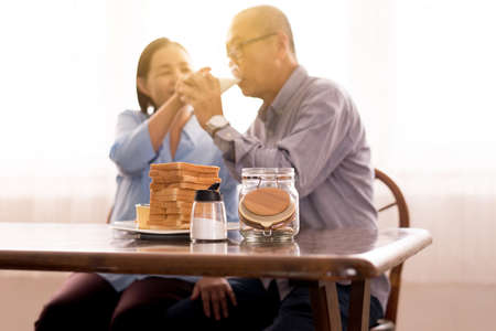 Blurred of Asian elderly couple drinking milk for breakfast together, Retirement lifestyle living concept